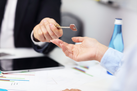 midsection: Midsection of businessman giving out a key to woman Stock Photo