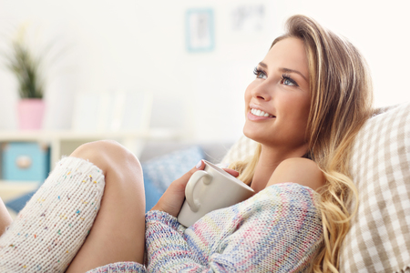 Picture showing adult woman sitting on sofa with coffee