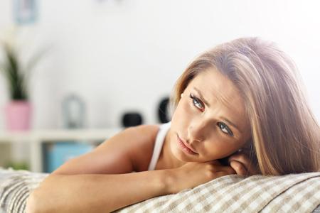femme triste: Photo montrant triste femme reposant sur un canapé