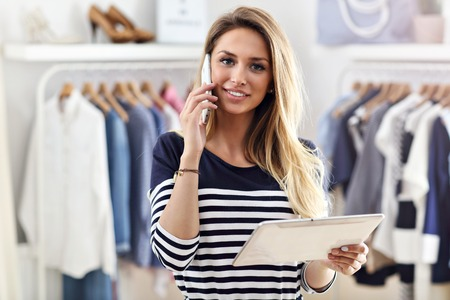 Happy woman in clothes shop holding tablet