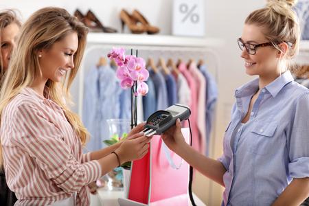 옷 가게에서 옷을 구입하는 여성