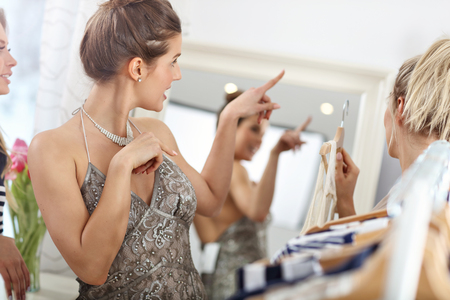 Happy woman trying on a dress in shop Stock Photo