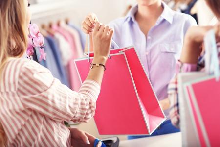 Primer plano de la mitad de la sección de la mujer cliente de recibir bolsas de la compra en la boutique