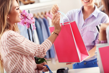 Closeup mid section of female customer receiving shopping bags in boutique Фото со стока - 73326477