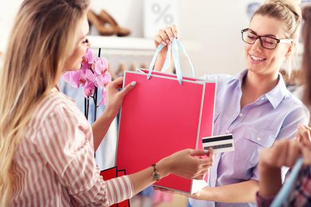 ブティックのショッピング バッグを受ける女性客 写真素材