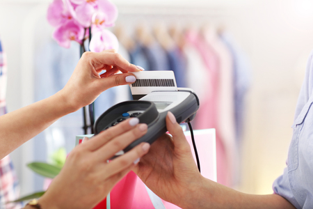shopping card: Closeup mid section of female customer paying in shop with credit card Stock Photo