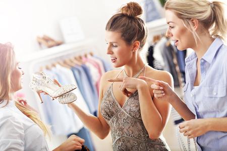 comprando zapatos: Mujer feliz tratando de elegir los zapatos