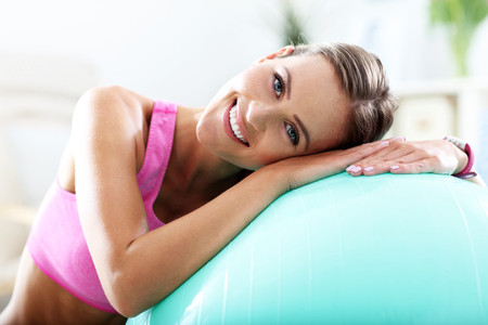 health and fitness: Smiling young woman with sports equipment at home.