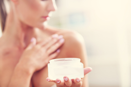 Picture of a fit woman holding lotion over her body Stockfoto