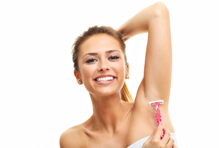 shaver: Adult woman shaving armpit with pink shaver isolated on white background