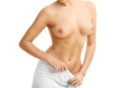 young woman nude: Adult woman posing in towel over white background