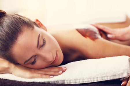 Mooie vrouw die chocolade massage in de spa Stockfoto - 77468876