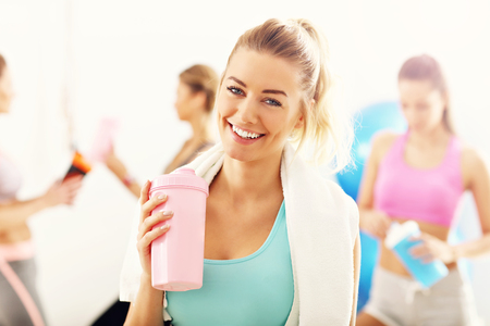 Portrait of beautiful mature woman with bottle smiling in health club