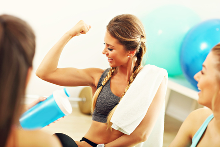 boasting: Young women group resting at the gym after workout