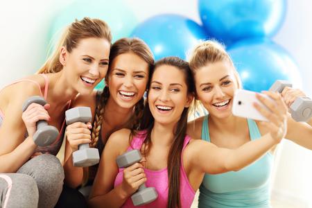 Grupo de mujeres jóvenes tomando selfie en el gimnasio después del entrenamiento