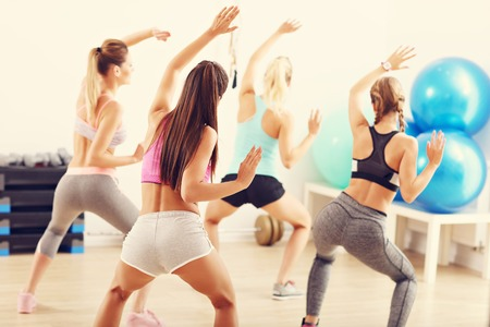 Group of happy people with coach dancing in gym Foto de archivo