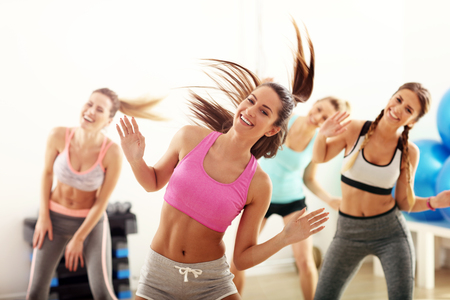 Group of happy people with coach dancing in gym Imagens