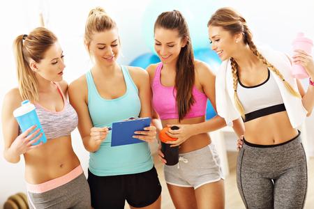 젊은 여성 그룹 체육관에서 건강 계획을 논의 스톡 콘텐츠