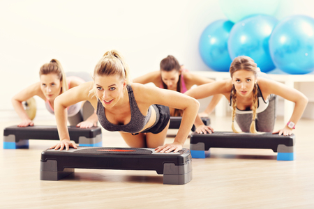Group of smiling people doing push-ups
