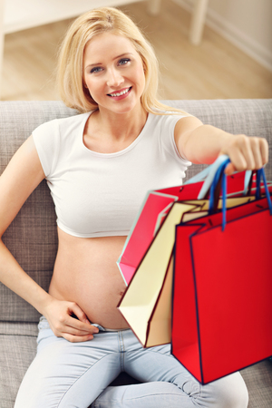 Pregnant woman using tablet for online shopping at home
