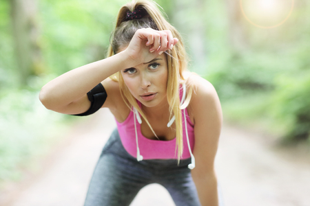 Exhausted woman jogging in the forest