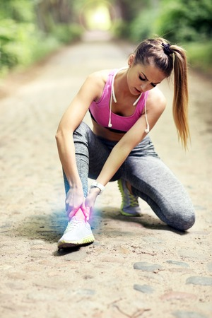 Female athlete runner touching foot in pain outdoors
