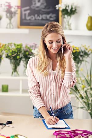 Vrouwelijke bloemist die in bloemwinkel werkt