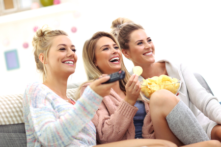 Three beautiful young women watching tv at home Zdjęcie Seryjne