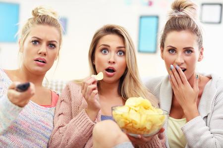 집에서 TV를보고 세 아름다운 젊은 여성 스톡 콘텐츠