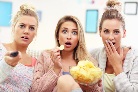 Three beautiful young women watching tv at home Stok Fotoğraf - 85267262