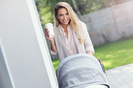 Trendy modern mother outside with a stroller