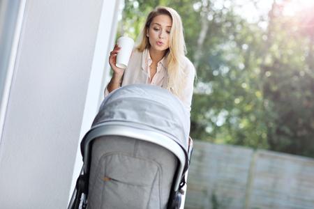 Trendy moderne moeder buiten met een wandelwagen