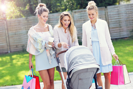 Trendy modern mother with friends outside with a stroller Stock Photo