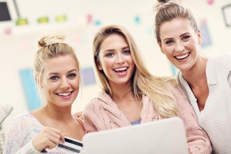 family sofa: Three beautiful young women shopping online