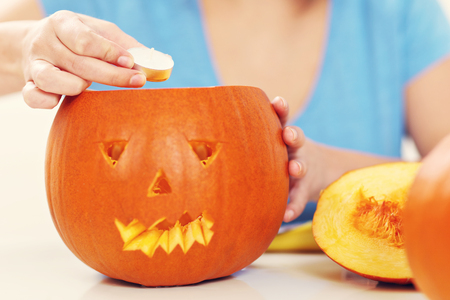 Young woman making jack-o-lantern in the kitchen