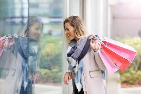 Happy woman window shopping in the city Stock Photo