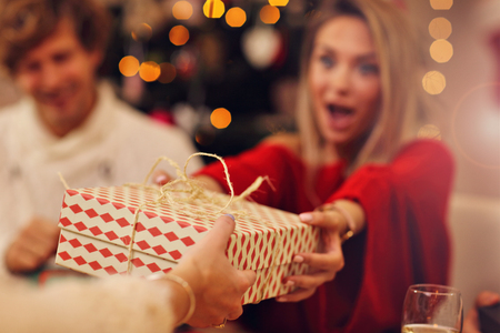 Group of friends giving Christmas presents at home Standard-Bild