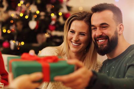 Groep vrienden geven kerstcadeautjes thuis Stockfoto
