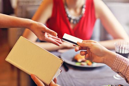 クレジットカードリーダーでレストランで支払う人々を示す画像