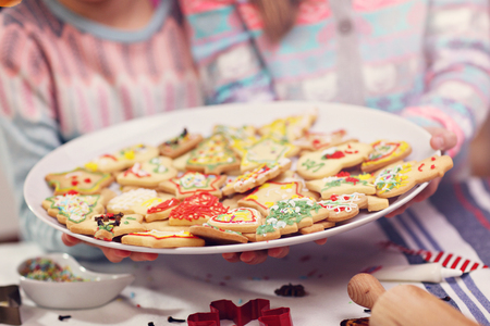 celebration: Happy little sisters preparing Christmas biscuits