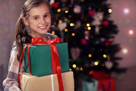 クリスマスの時期にプレゼントでポーズをとる幸せな女の子 写真素材