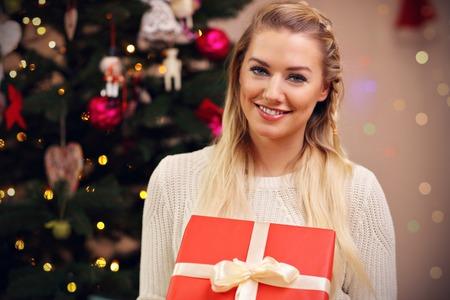 クリスマスの時期にプレゼントでポーズをとる幸せな女性