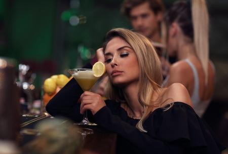 Junge Frau , die alleine in der Stange mit einem Coctail sitzt Standard-Bild - 90910590
