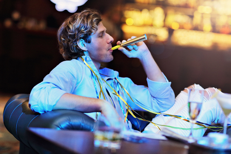 Young man sitting alone in bar with a glass of whisky Stock Photo - 90910687