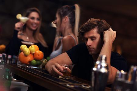 Junger Mann , der alleine in der Stange mit einem Glas Whisky sitzt Standard-Bild - 90910688