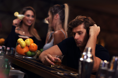 Young man sitting alone in bar with a glass of whisky