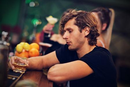 Junger Mann , der alleine in der Stange mit einem Glas Whisky sitzt Standard-Bild - 90910692
