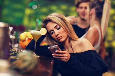 Young woman sitting alone in bar with a coctail Stock Photo - 90910233