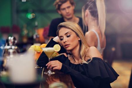 Jonge vrouw zit alleen in de bar met een coctail Stockfoto