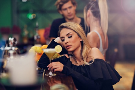 Young woman sitting alone in bar with a coctail